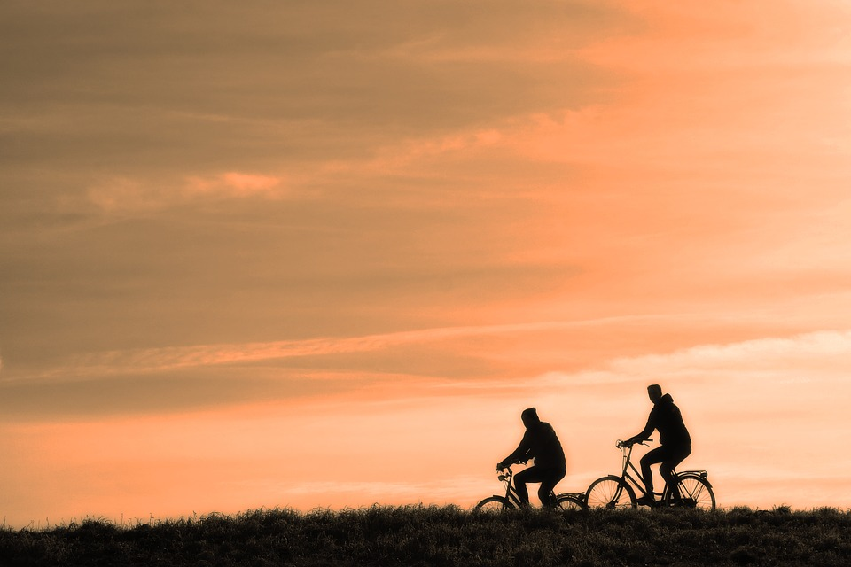 two cyclists in the sunset